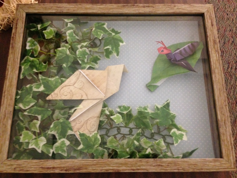 Origami bird sits in foliage overlooking an origami ant on a leaf