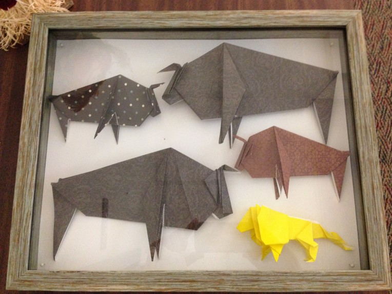 Four origami oxen and an origami lion mounted in a shadow box