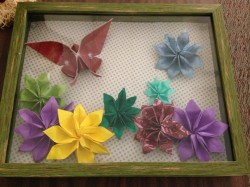Origami butterfly mounted in a shadow box with an assortment of origami flowers