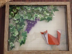 Origami fox, foliage, and grapes in a shadow box