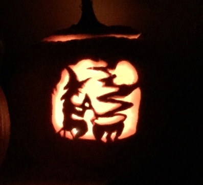 carved pumpkin displaying silhoutte of witch mixing her cauldron